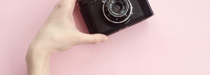 an arm is reaching upwards with the hand holding a black camera against a pink background.