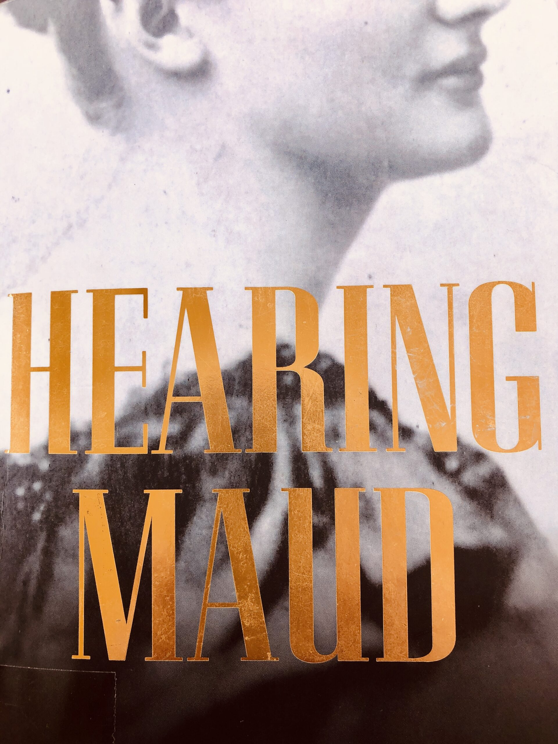 This a picture of the book cover. It has a black and white picture of a woman from early in the 1900s, facing side on to the camera. The words 'Hearing Maud' overlay the picture and are in gold.