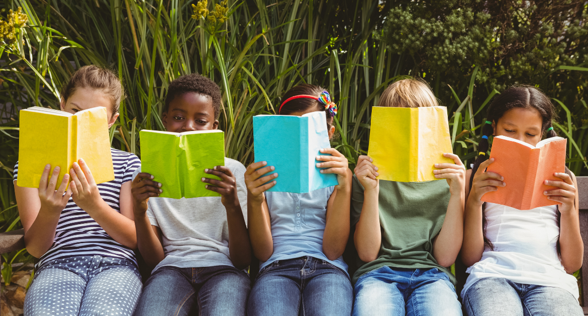 Five children are sitting side-by-side on a bench reading a book each.