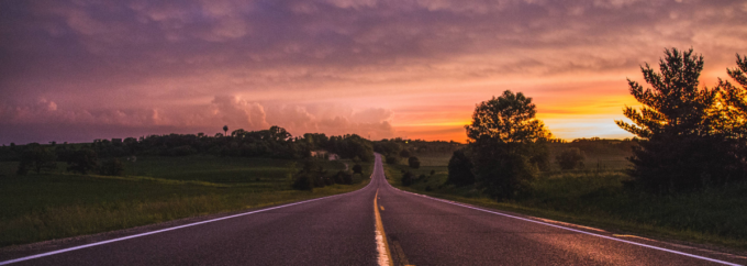 A photo of a road at sunset. There are double yellow lines in the middle of the road.
