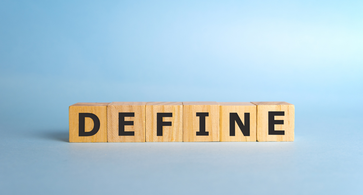 The word 'Define' is written on wooden blocks against a blue background.